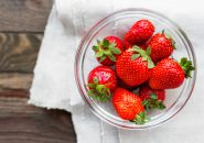 Fresh juicy strawberries in glass bowl. Rustic background with homespun napkin. Top view. Place for text.